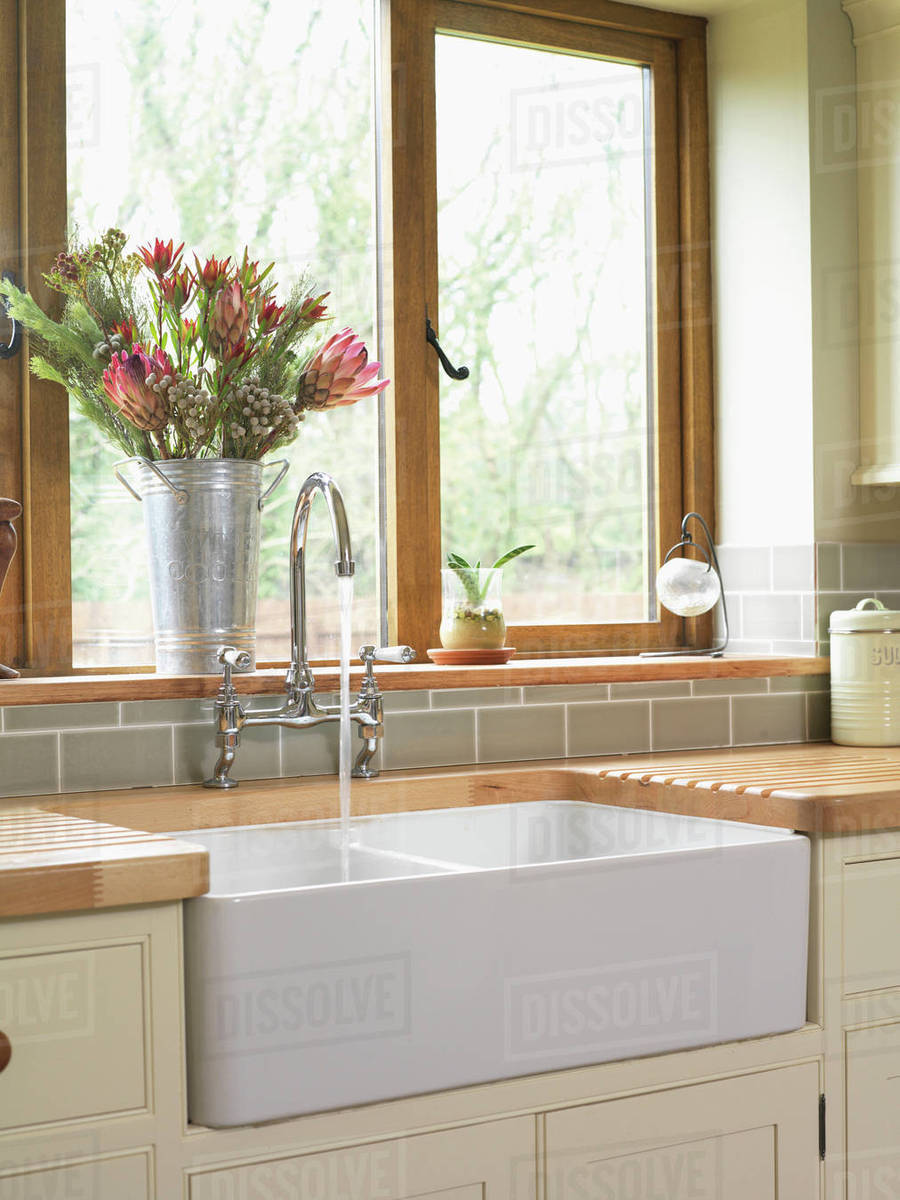 Water Running From Tap Fitting Into Kitchen Sink Stock Photo Dissolve