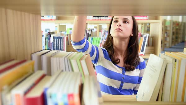 Smiling teenager student girl in school library holding books Royalty-free stock video