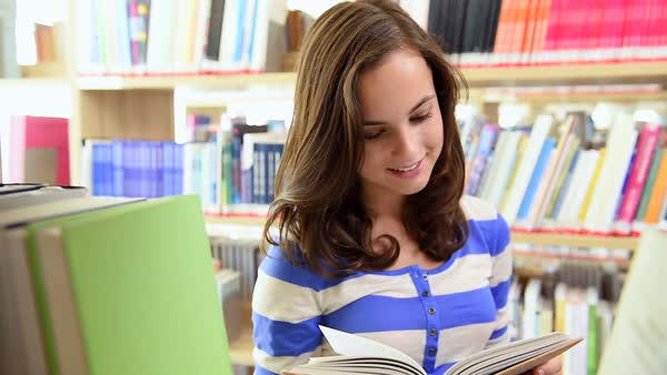 Cheerful student girl choosing book in college library smiling at camera Royalty-free stock video
