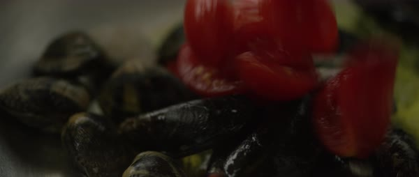 Hand-held shot of a person adding tomatoes to frying mussels Royalty-free stock video