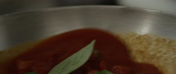 Hand-held shot of a person tossing tomato sauce in a pan Royalty-free stock video