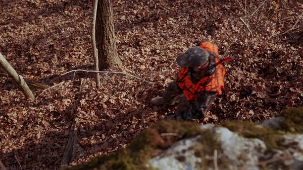Overhead shot from a rocky cliff looking directly overhead as a hunter walks through frame. Royalty-free stock video