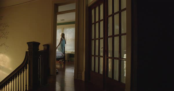 Looking down a dark hallway into a woman's bedroom. The woman crosses in front of the door wearing a 1940s vintage blue nightgown. Royalty-free stock video