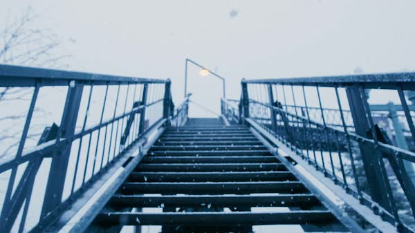 Snow covers the stairs leading up to a walking bridge. Royalty-free stock video