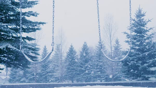 Empty swings sway in the midst of a heavy snowstorm. Royalty-free stock video