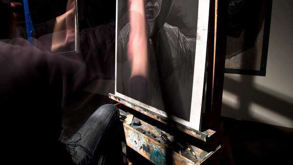 Motion timelapse of an artist working on a charcoal self-portrait. Royalty-free stock video