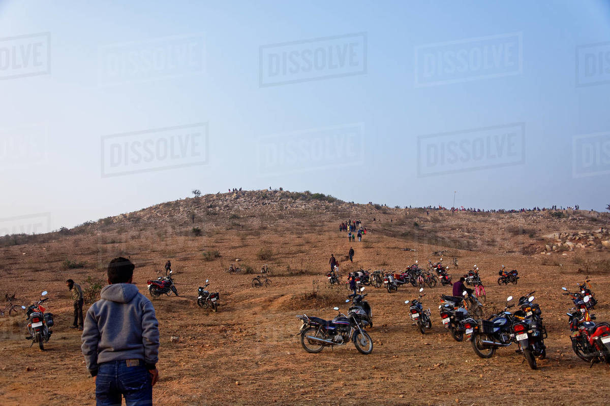 People are climbing on an Indian hill keeping motorcycle at the bottom Royalty-free stock photo