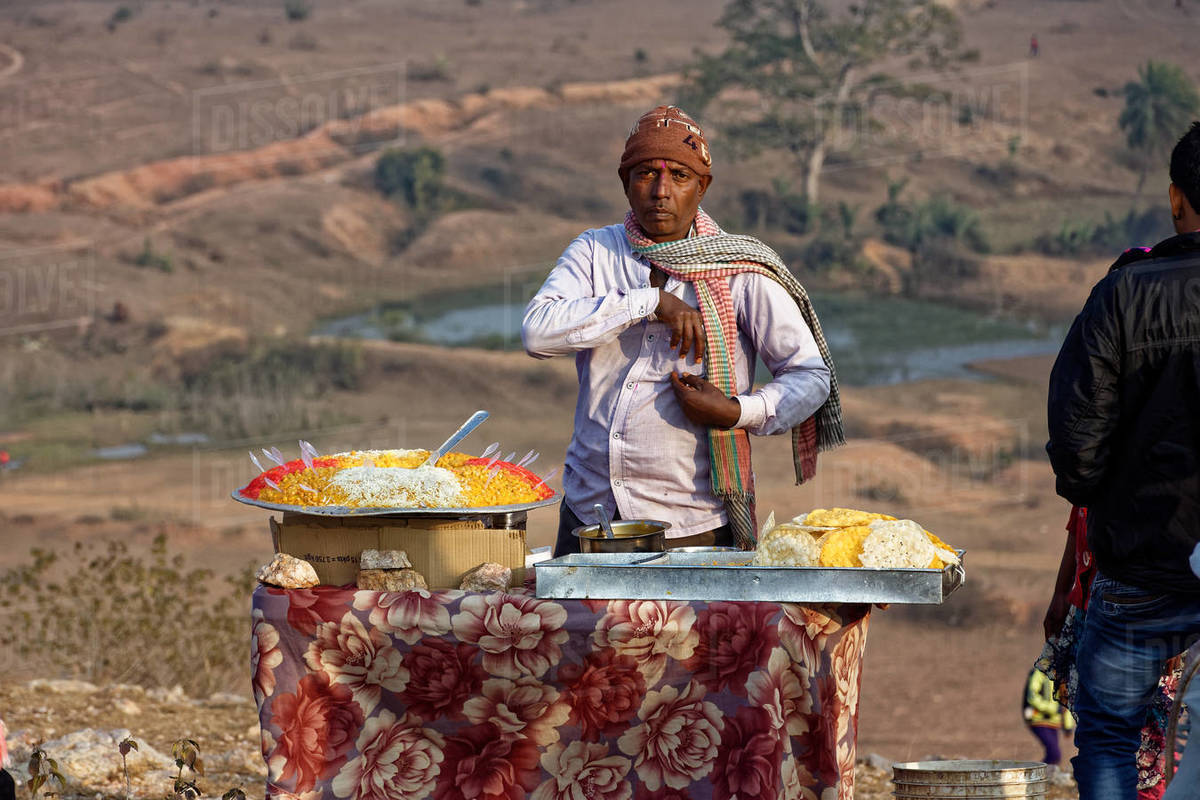 An Indian business man is selling street food on a hilltop fair. Royalty-free stock photo