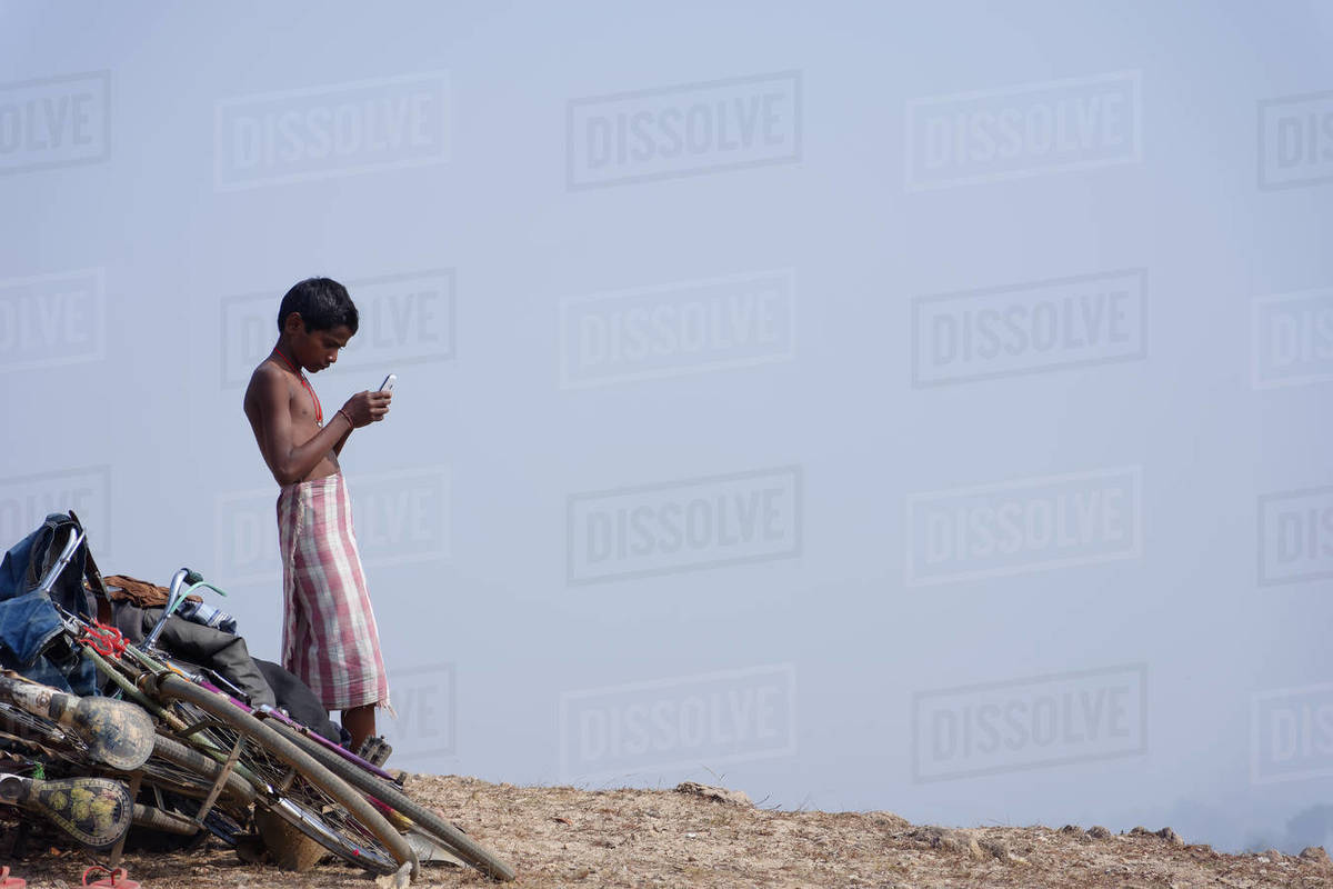 A bare body black child is watching his cellphone under blue sky Royalty-free stock photo