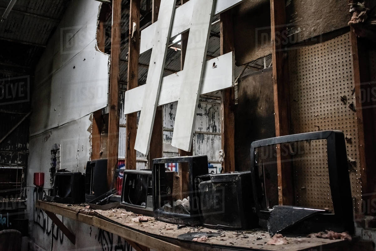 Broken televisions on a messy shelf, pound symbol hanging above. Royalty-free stock photo