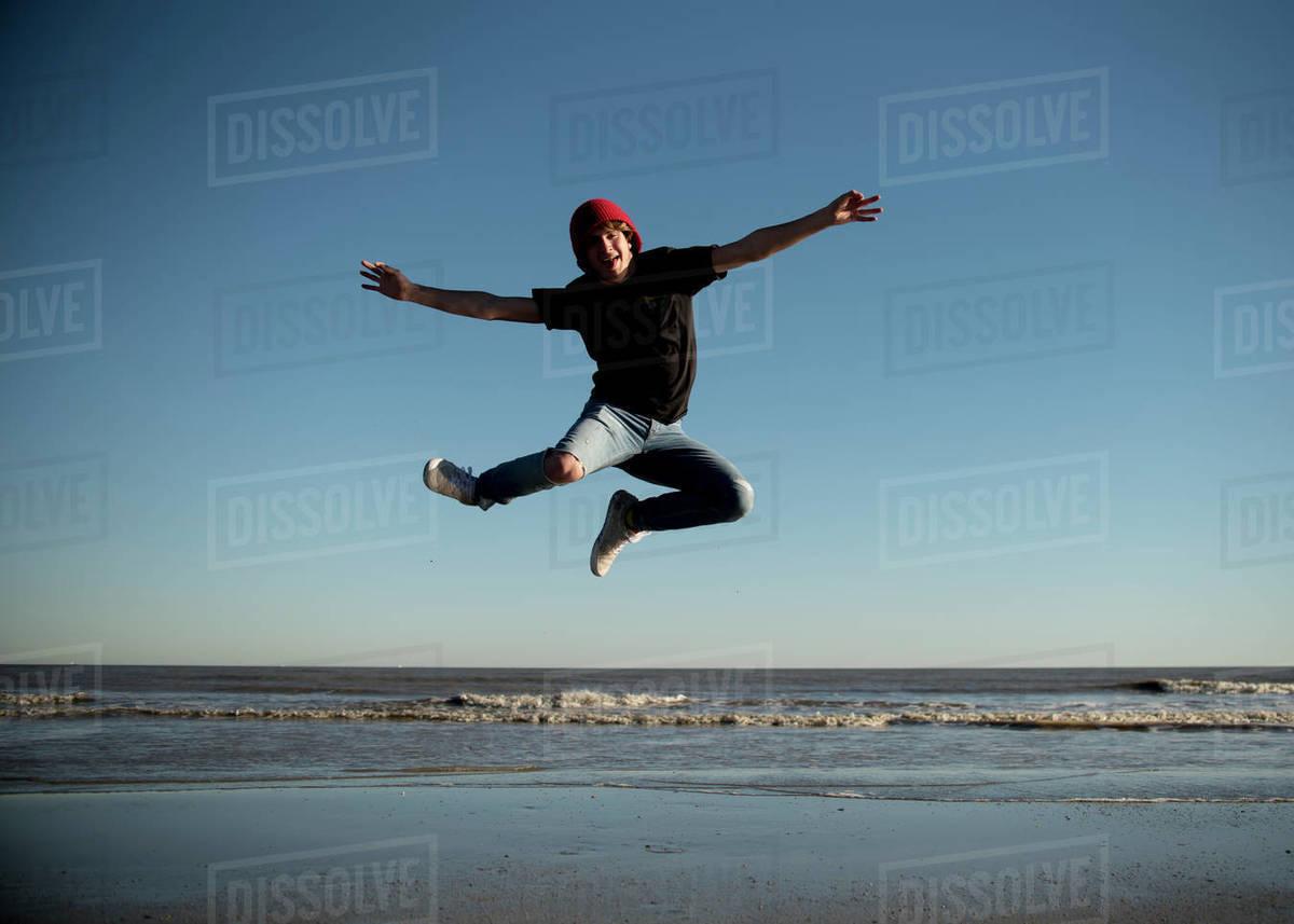 Happy teenage boy jumping on the beaches of Galveston, Texas. Royalty-free stock photo