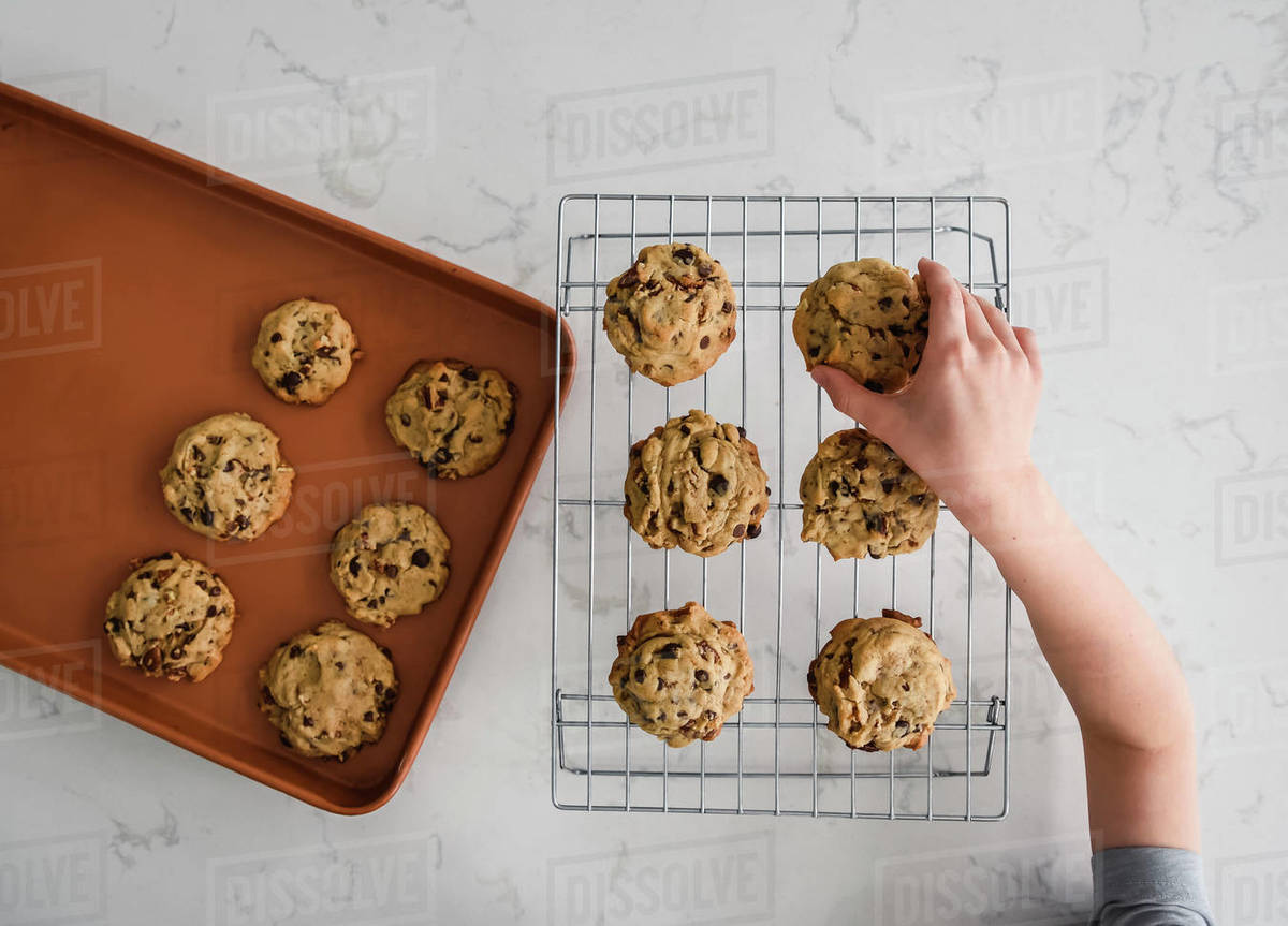 Hand of young child reaching to take a cookie off of a cooling rack Royalty-free stock photo