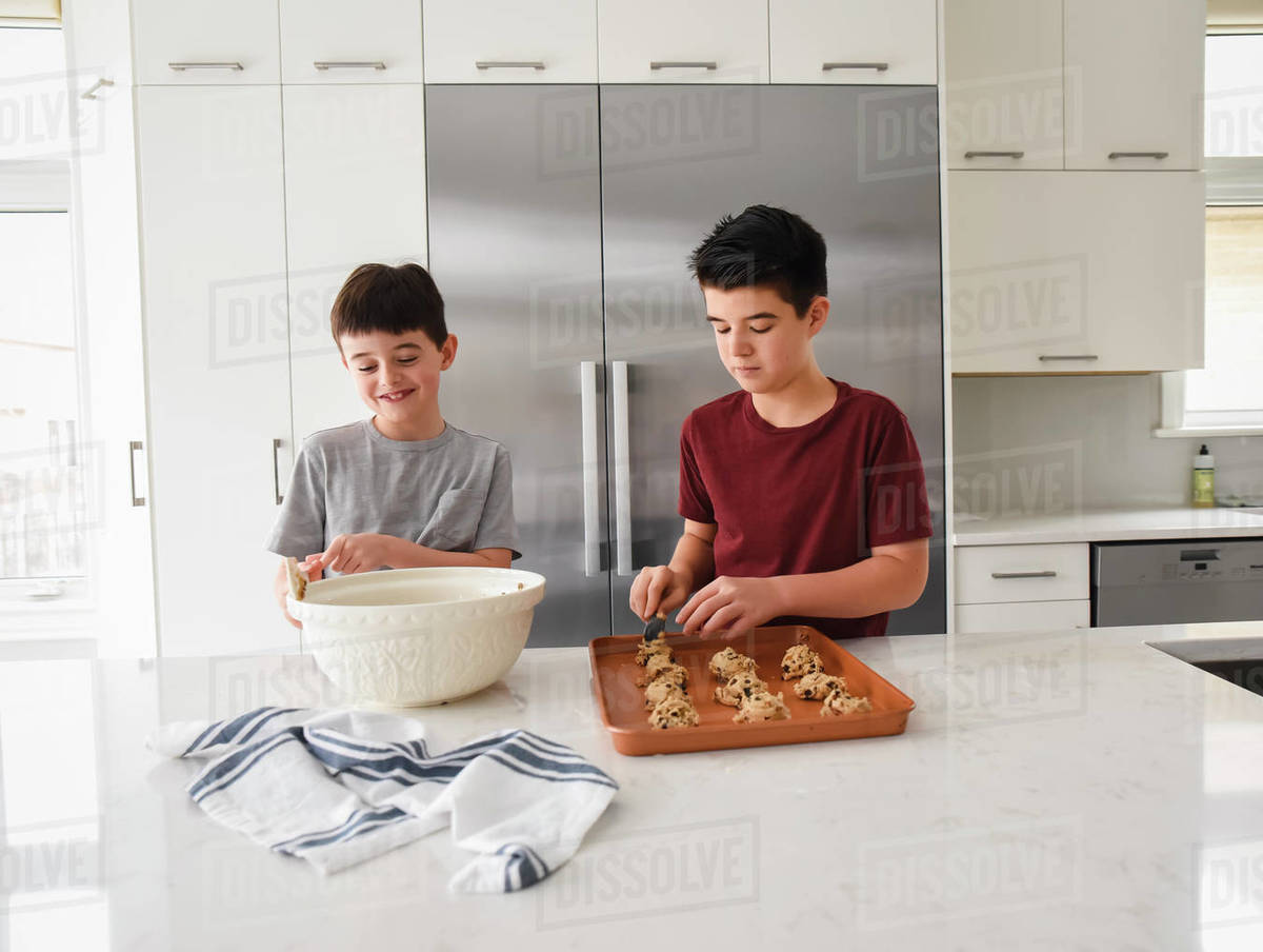Two boys happily baking cookies together in a modern kitchen Royalty-free stock photo