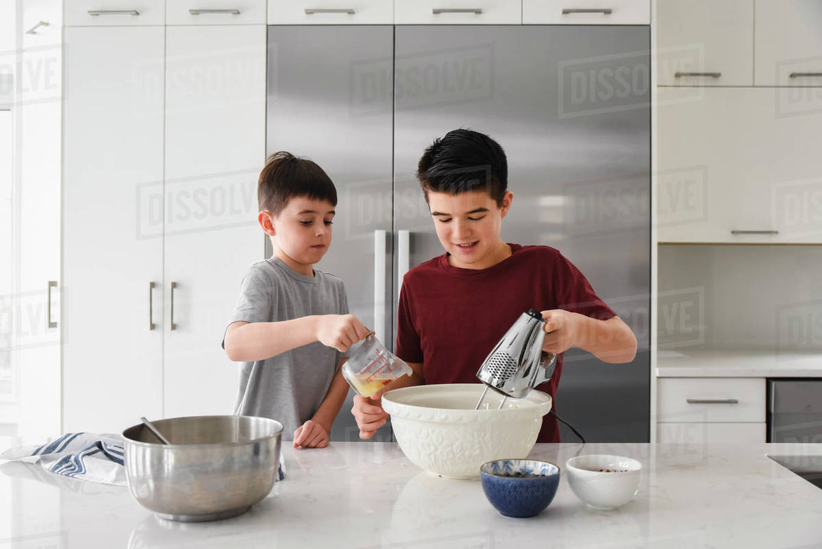 Two boys using a mixer and measuring cup in a modern kitchen Royalty-free stock photo
