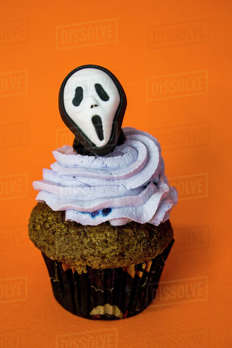 Funny halloween monster mask cupcake on an orange background Royalty-free stock photo