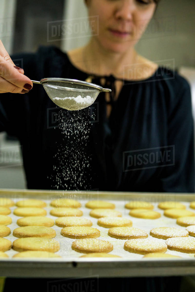 Black dressed woman is putting a cascade of sugar powder to the dough Royalty-free stock photo