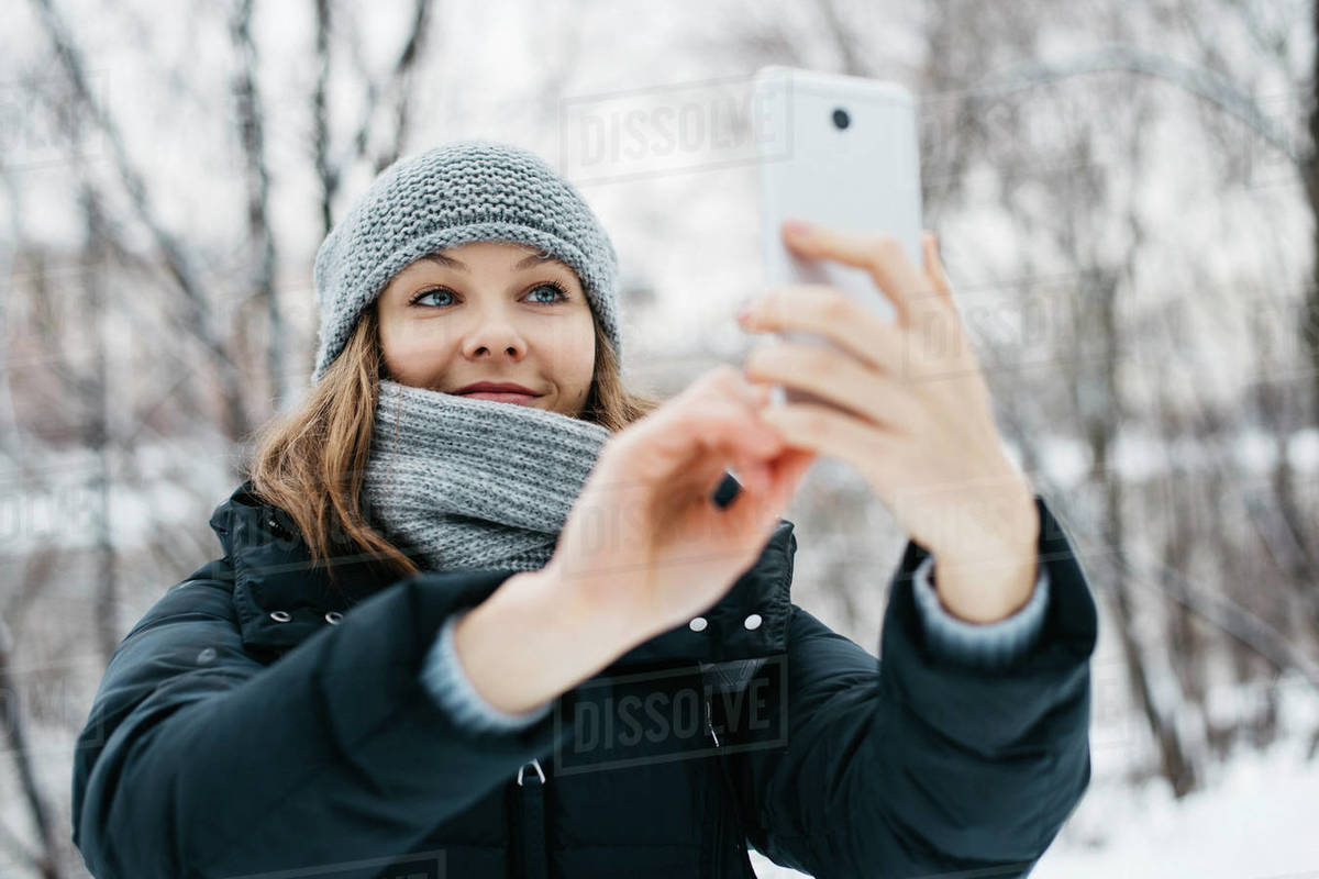 Smiling young woman getting a selfie on her phone in winter park Royalty-free stock photo