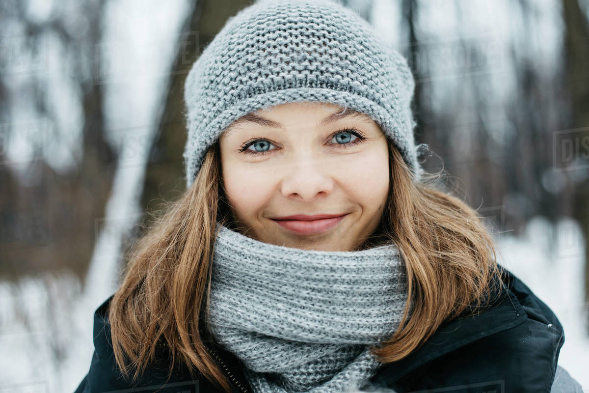 Closeup portrait of happy young woman in winter park looking at camera Royalty-free stock photo