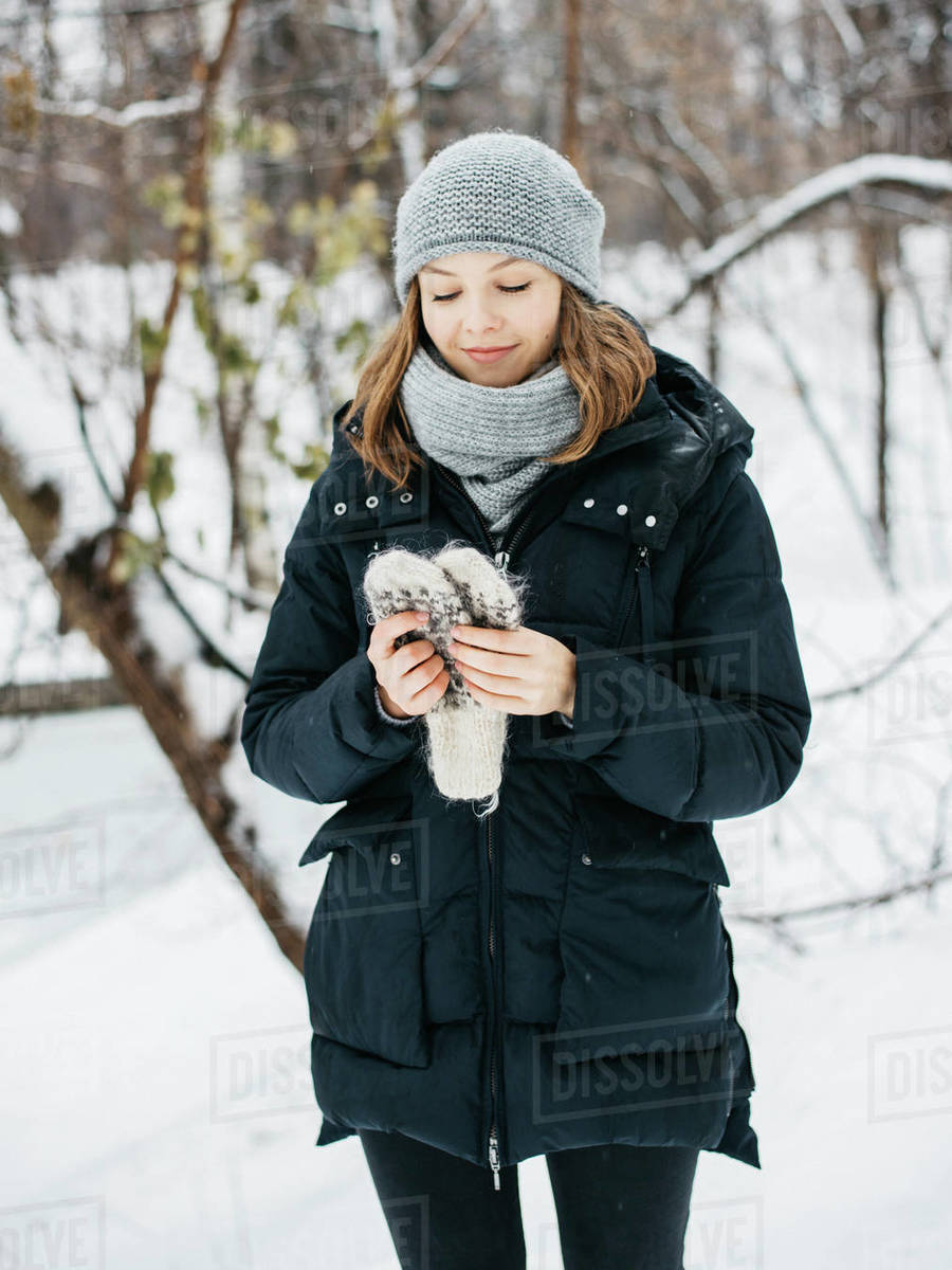 Young woman holding woolen mittens in her hand in winter park Royalty-free stock photo
