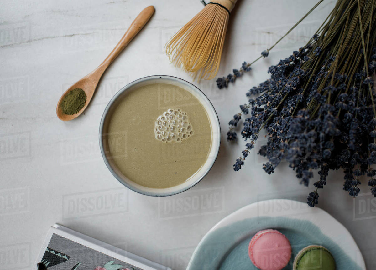 Matcha tea latte and macarons on a table with flowers Royalty-free stock photo