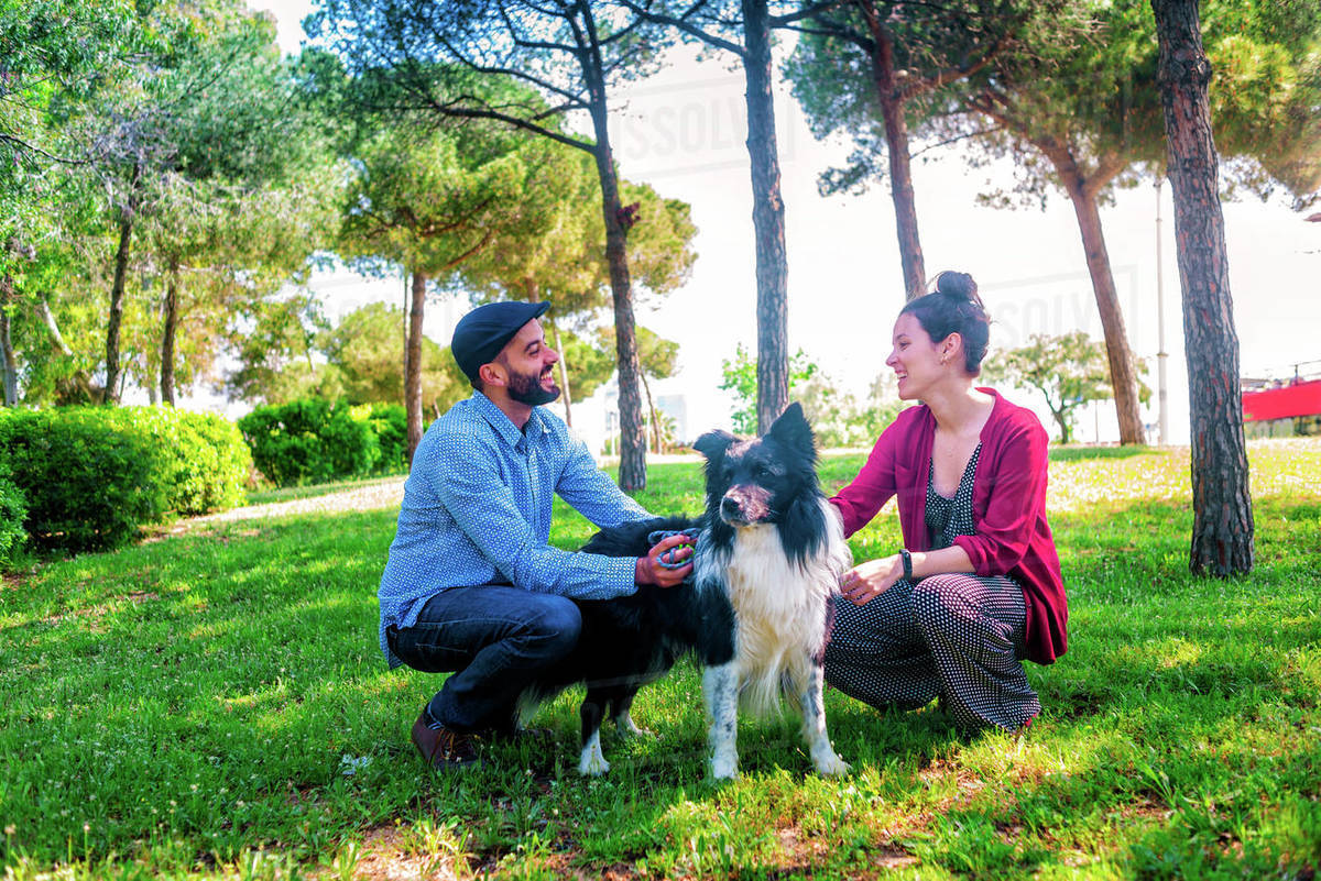 Young couple enjoying with a dog in a city park Royalty-free stock photo