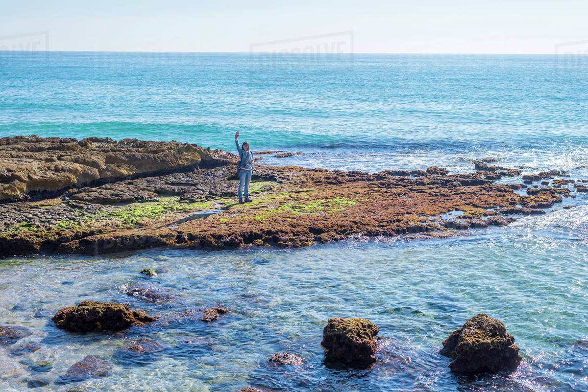 Woman waving standing on the rocks againts the blue sea Royalty-free stock photo