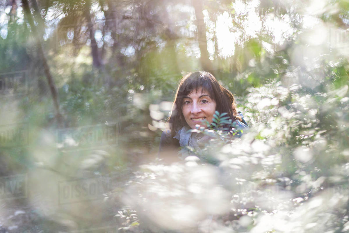 Front view of a backpacker looking away while standing into the forest Royalty-free stock photo