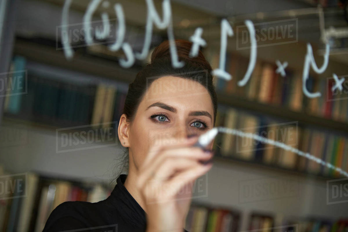 Educated business woman writing down mathmetical formula on glass Royalty-free stock photo