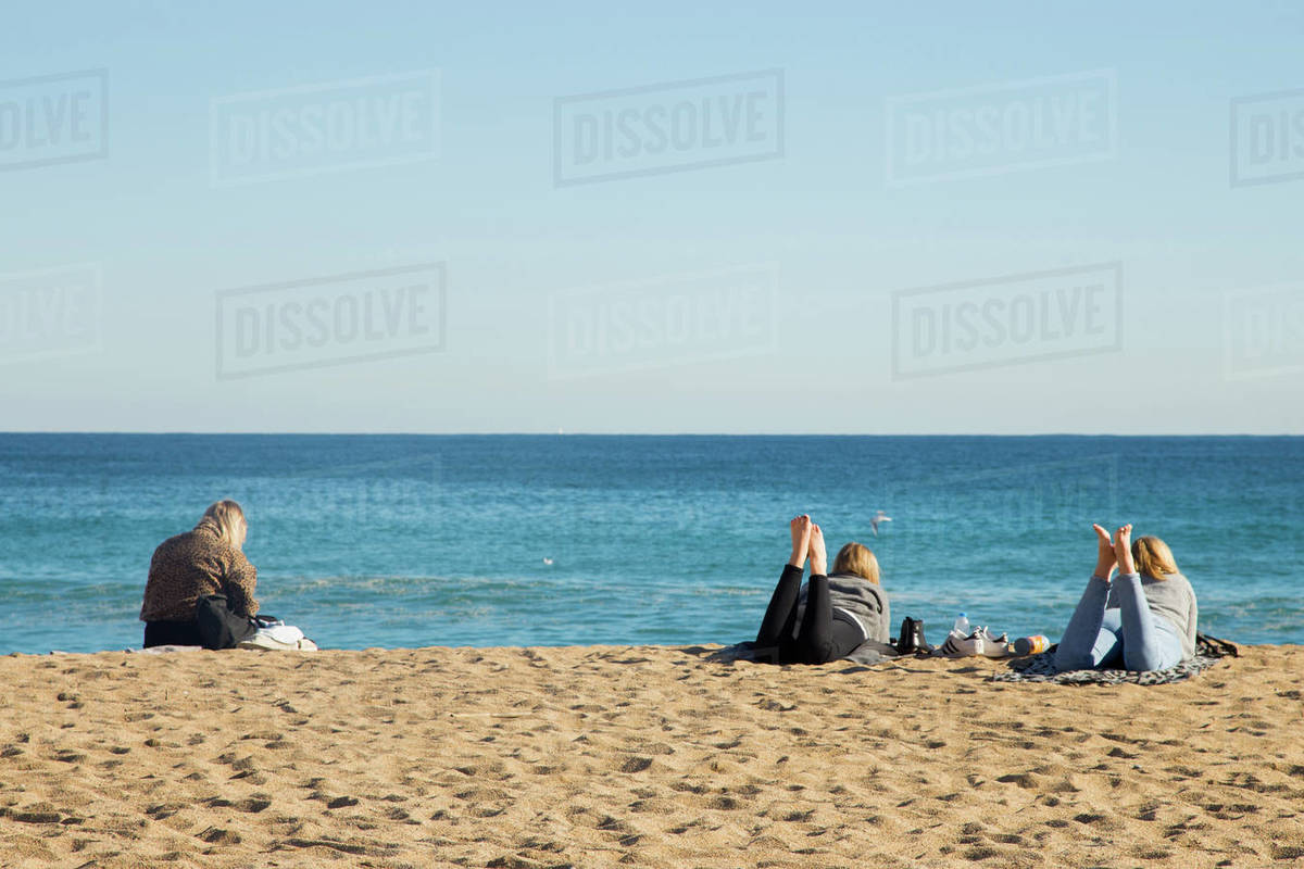Young women chilling in Barcelona Beach in Winter Royalty-free stock photo