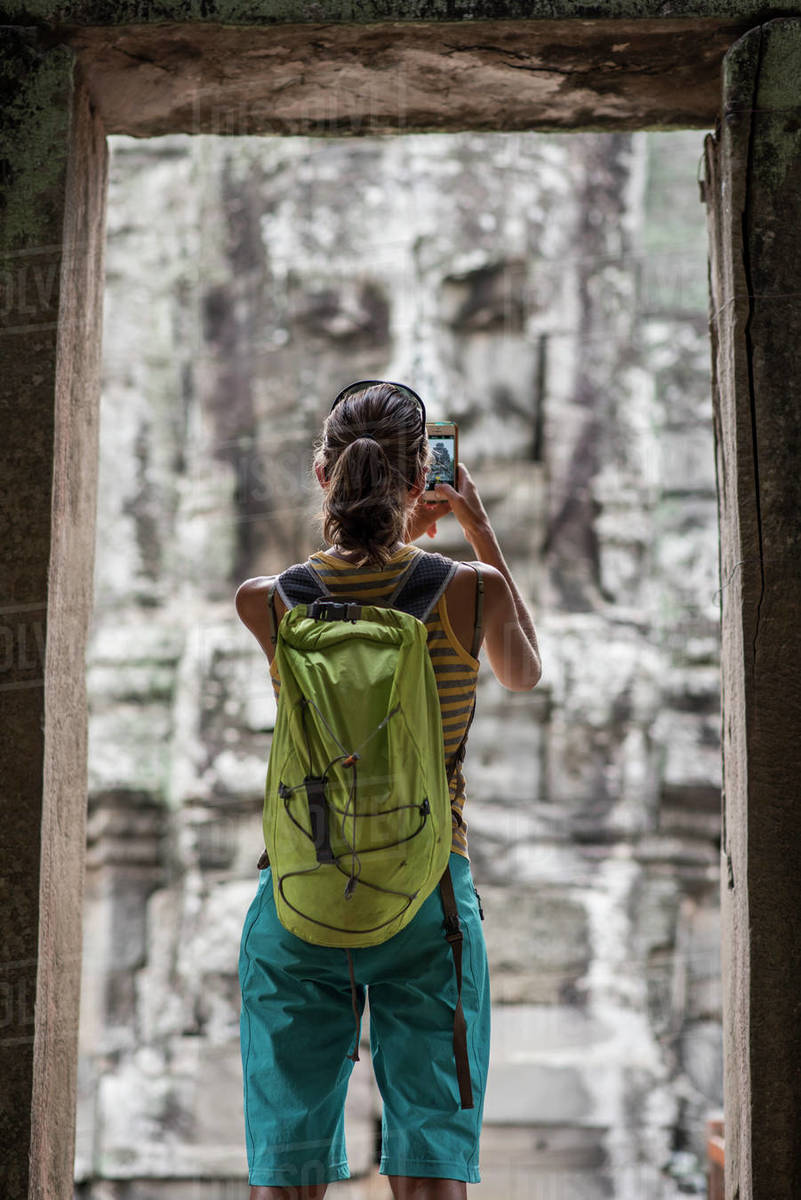 A female tourist taking pictures at Bayon, ankor Thom temple, Angkor Wat, Siem Reap, Cambodia. Royalty-free stock photo