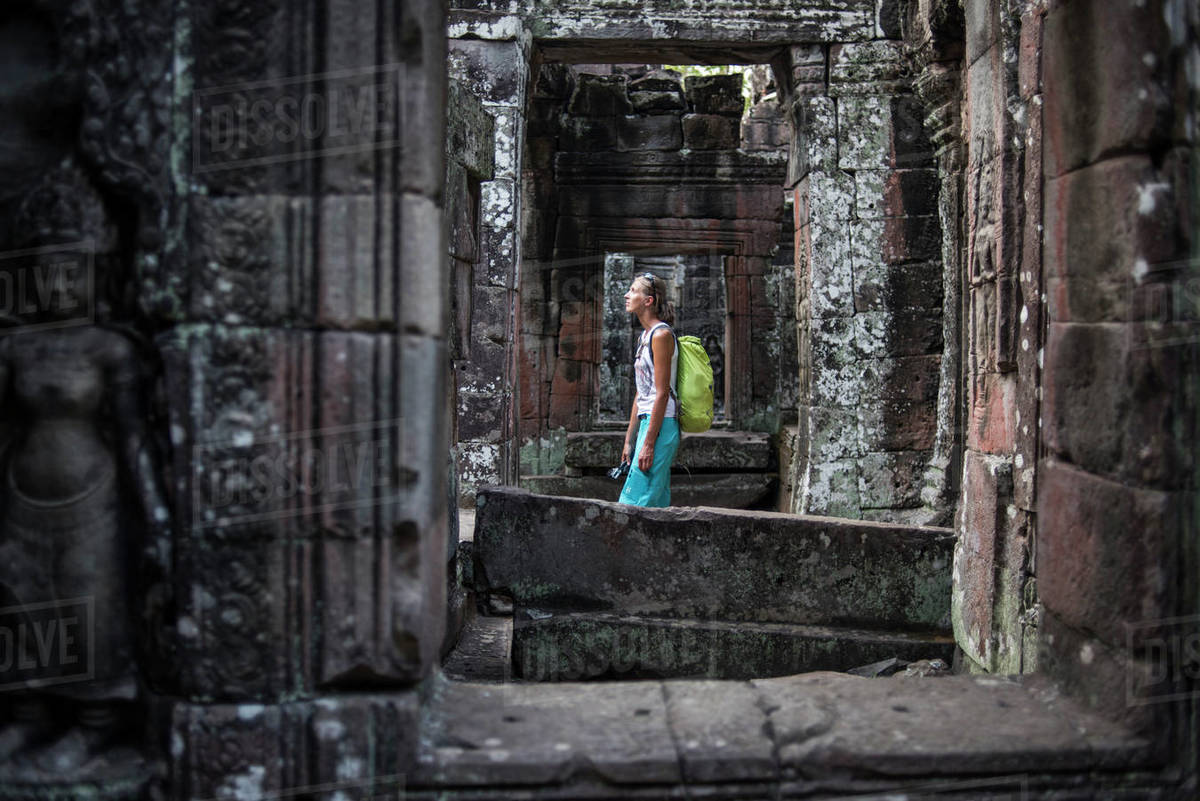 A female toursit walk around the Ta Prohm temple in Angkor Wat, Siem Reap, Cambodia. Royalty-free stock photo