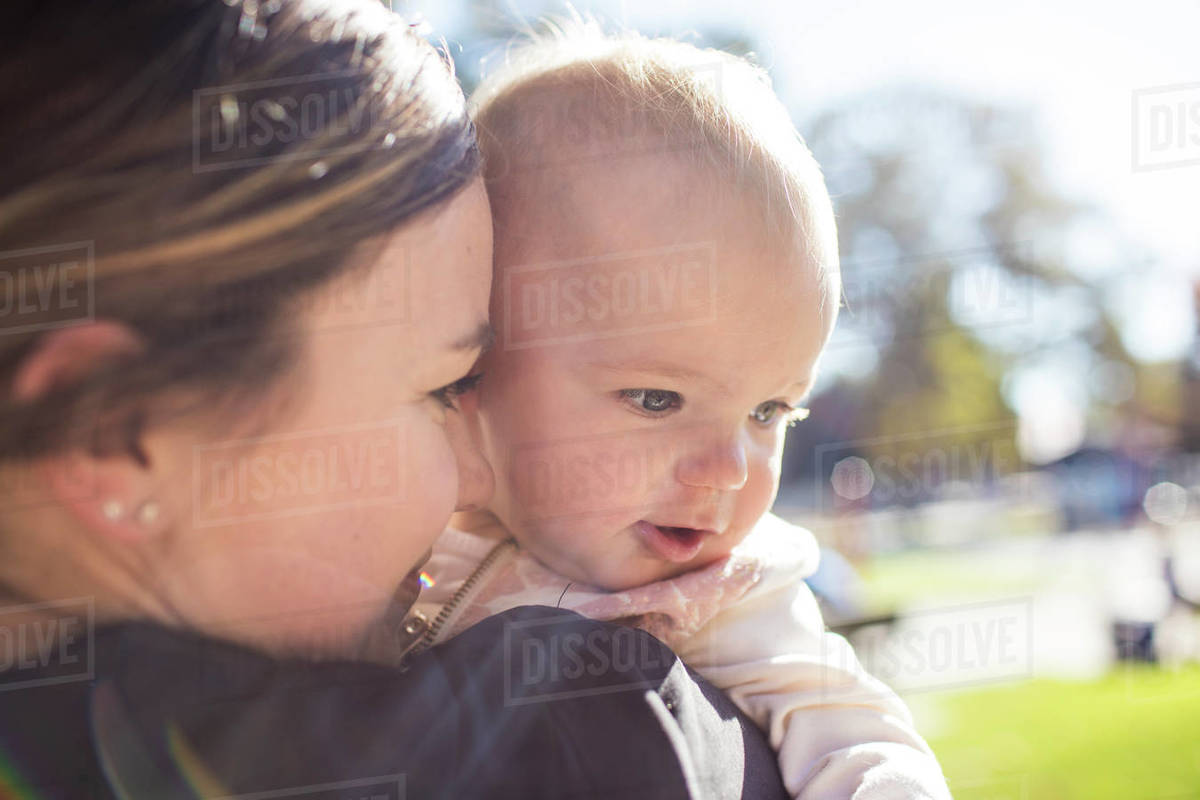 Close up of Mother holding her daughter at the park. Royalty-free stock photo