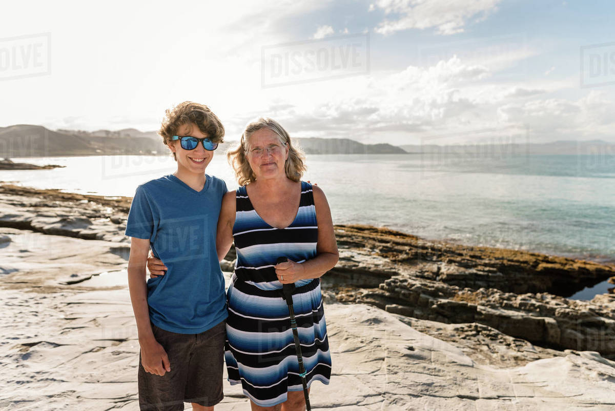 Grandmother and teenage grandson smiling together at a rocky beach Royalty-free stock photo