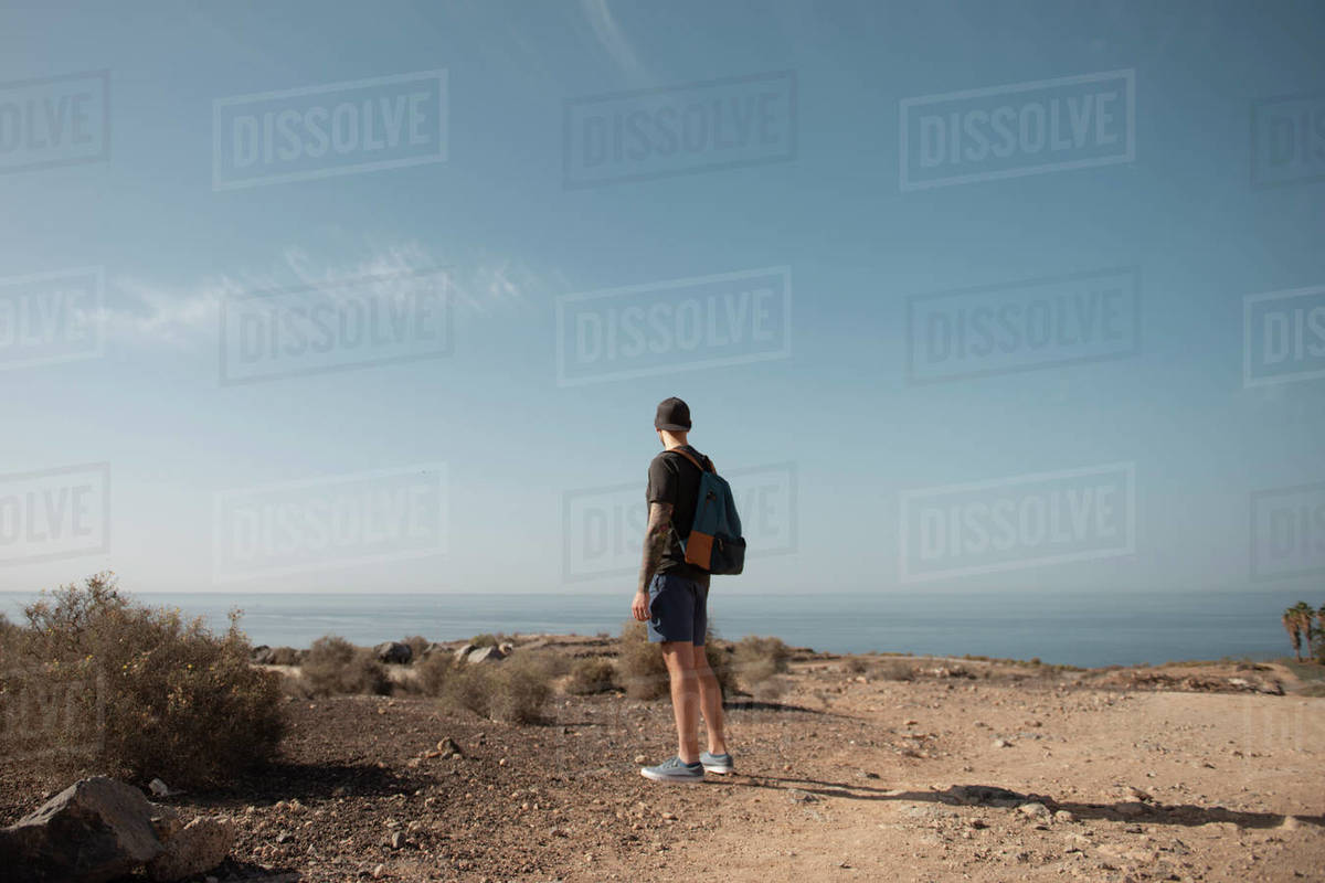 Full Length Of Young Man With Backpack Looking At The Atlantic Ocean Royalty-free stock photo