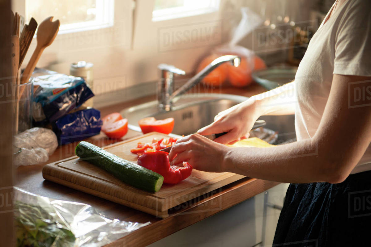 Young woman cooking vegetarian salad with red bell pepper at home Royalty-free stock photo