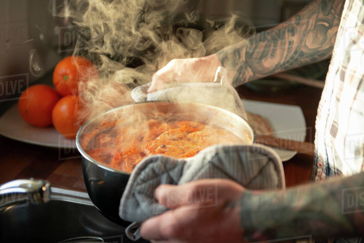 Man holding metal pan full of boiled shrimps while steam is coming out Royalty-free stock photo