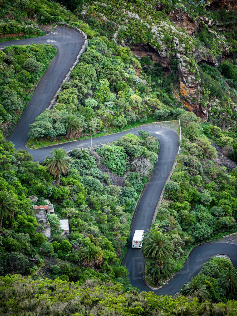 Car moving on winding road through the mountains covered by lush trees Royalty-free stock photo