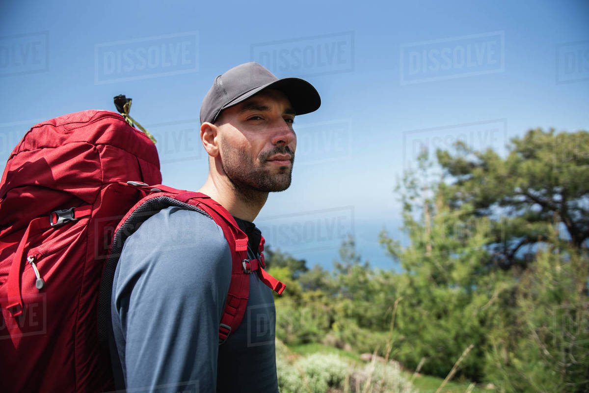 Pensive man with backpack standing and looking away against blue sky Royalty-free stock photo