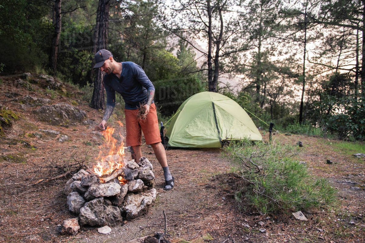 Man burning campfire near tent amidst trees in forest in the evening Royalty-free stock photo