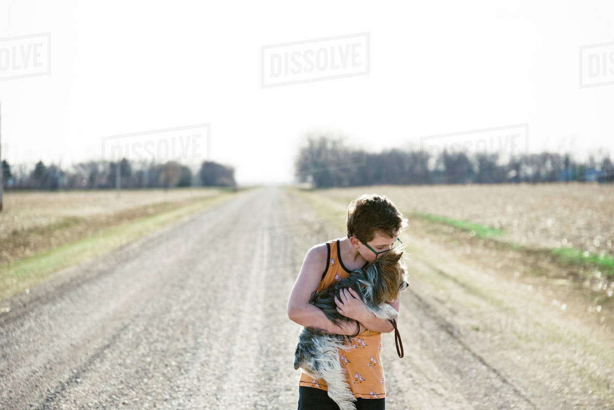Boy showing his friendship with his dog in a countryside setting. Royalty-free stock photo