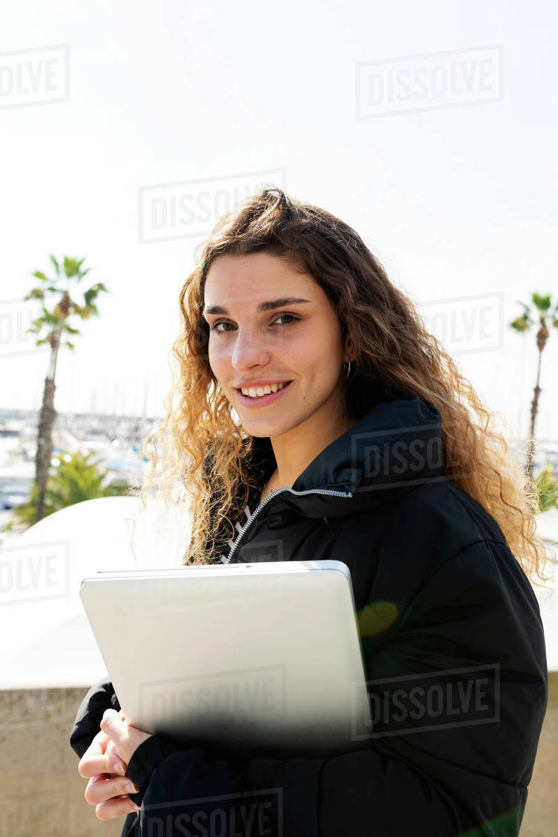 Young brunette student holding a laptop walking outdoor Royalty-free stock photo