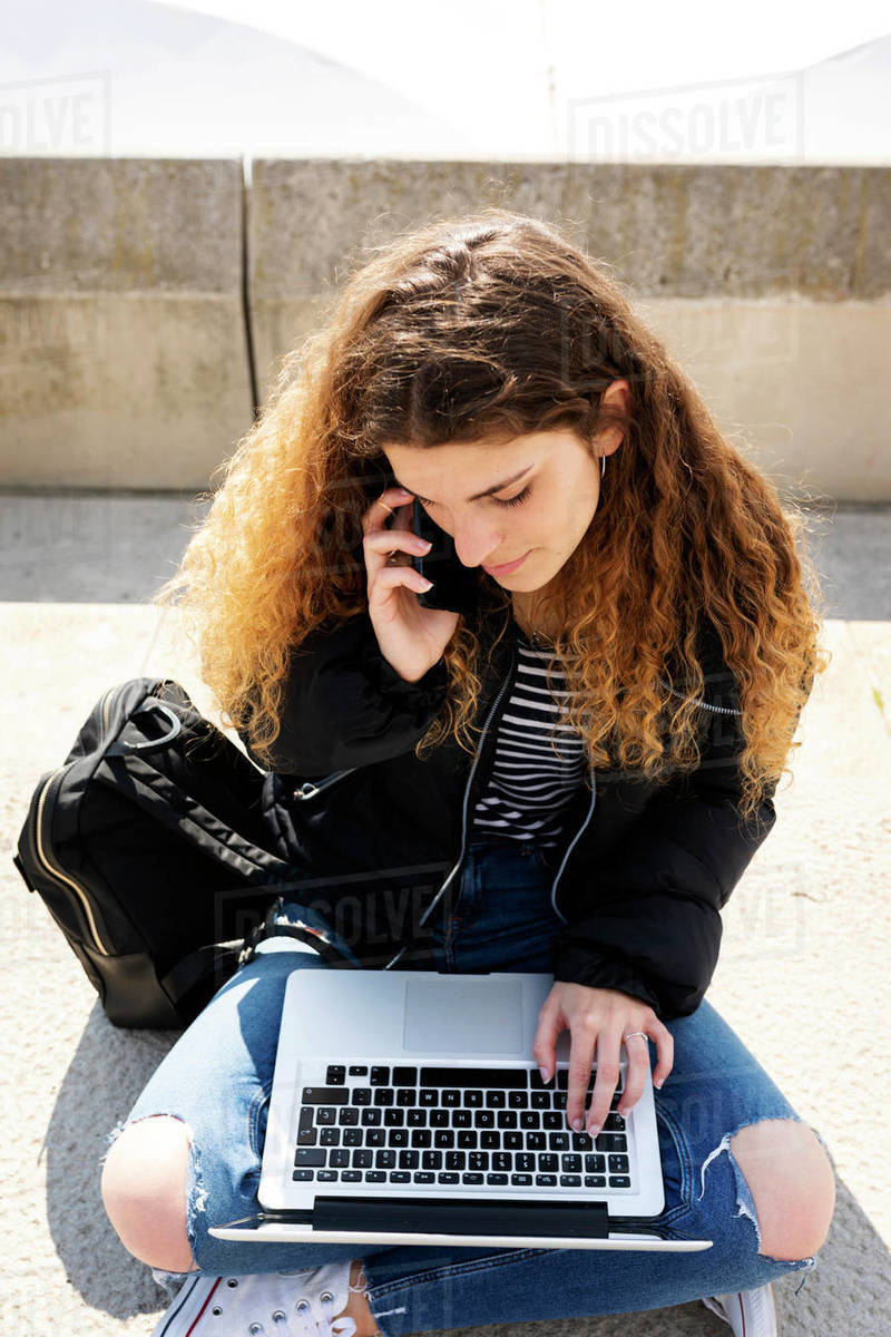 Young student sitting on stairs in the city- working with laptop Royalty-free stock photo