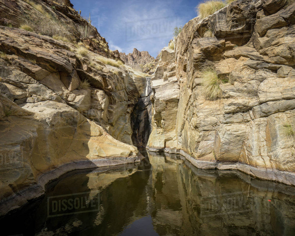 Desert landscape with rock walls and a natural pool of water Royalty-free stock photo