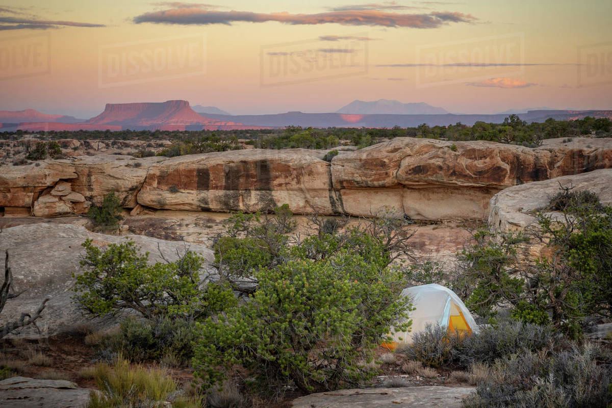 Tent in southwest desert landscape with mountains, buttes, and mesas Royalty-free stock photo