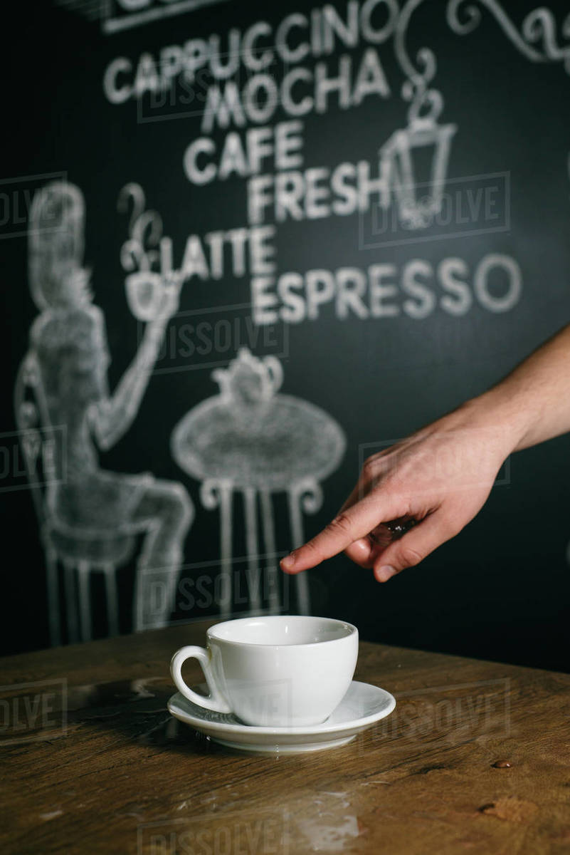 A man points his finger in an empty cup of coffee. Royalty-free stock photo