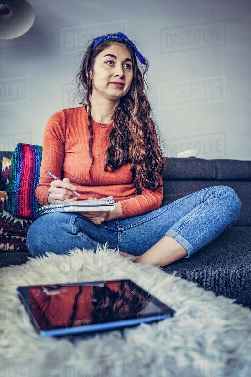 Young mixed race woman is studing in home, writting in notebook Royalty-free stock photo