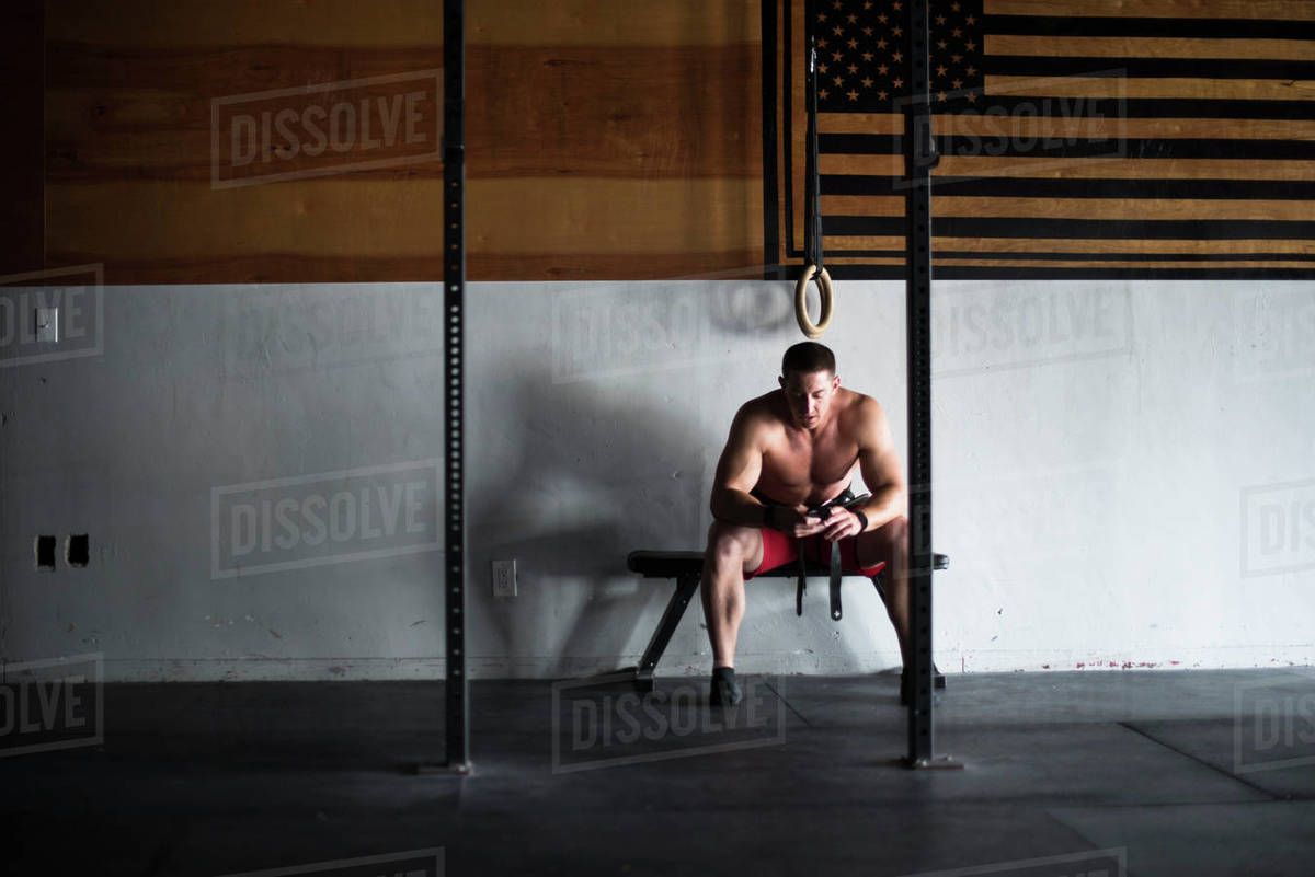 An athlete takes a break during a workout to look at his phone. Royalty-free stock photo