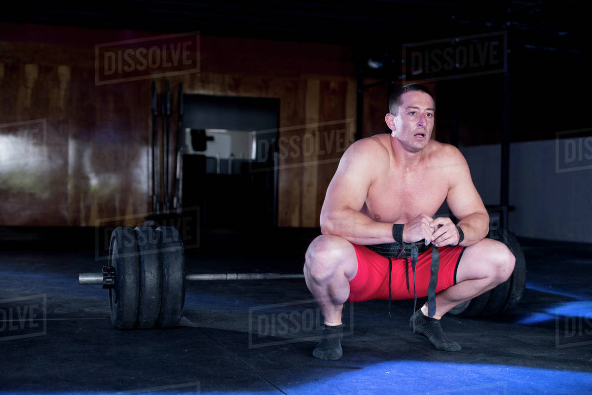 A body builder kneels down to rest after deadlifting. Royalty-free stock photo