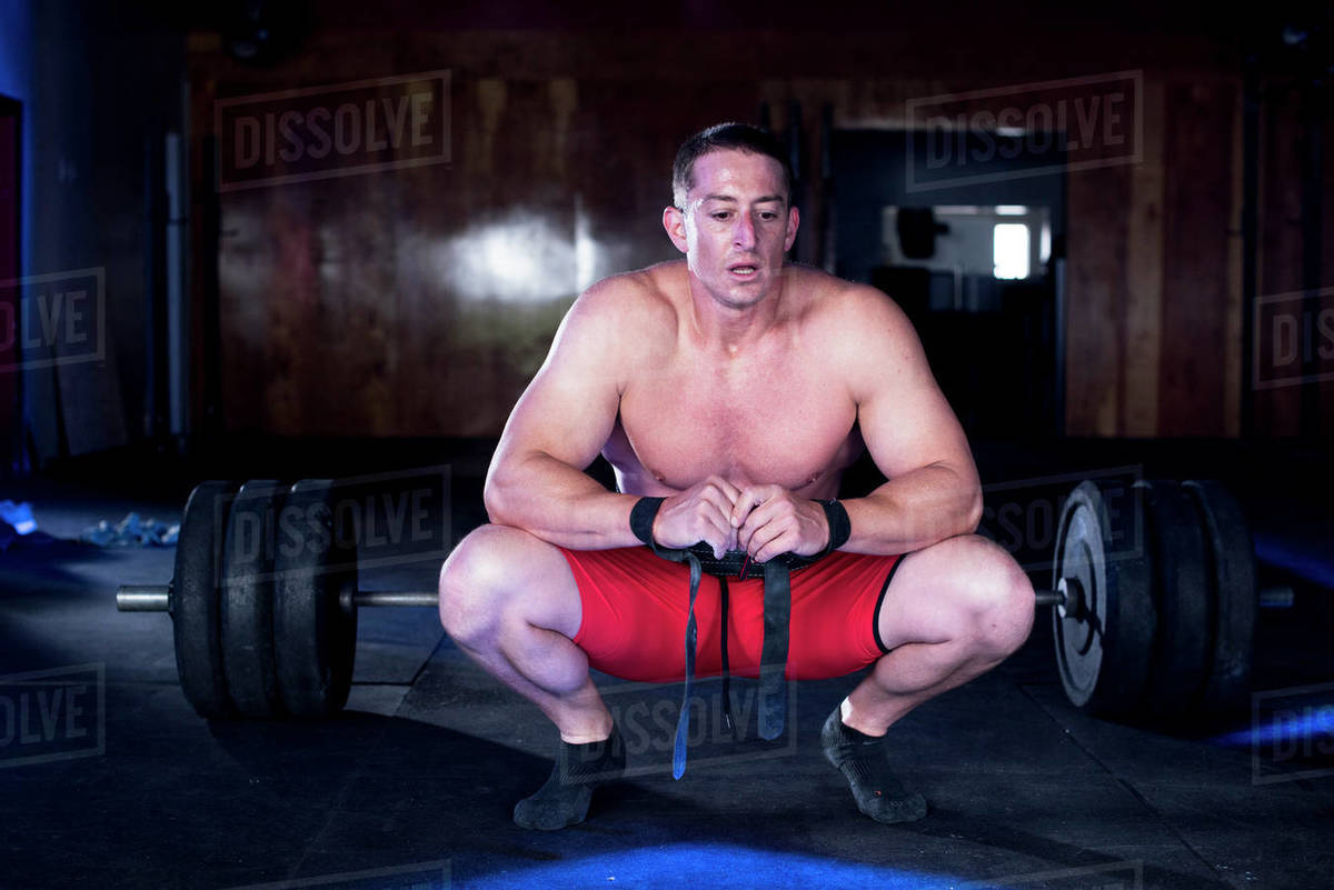 A weightlifter kneels in front a barbell after deadlifting. Royalty-free stock photo