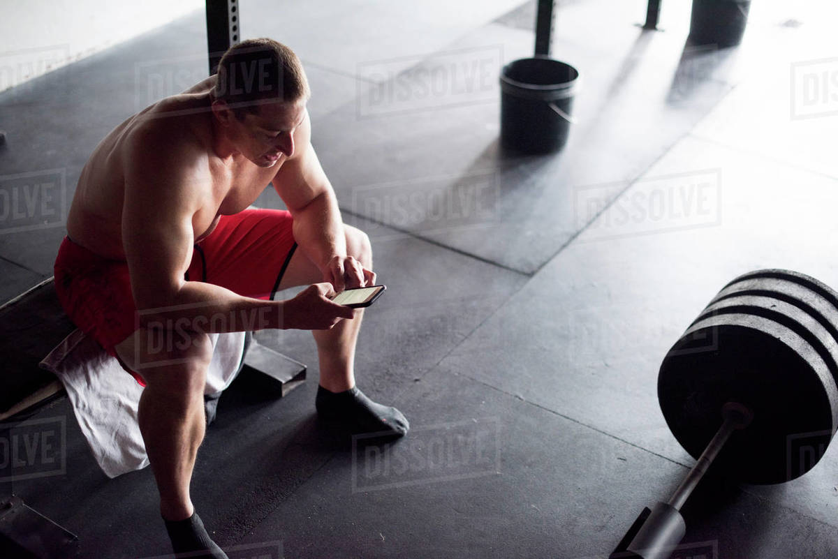 A weightlifter takes notes in his phone after a workout. Royalty-free stock photo